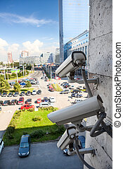 Video surveillance cameras on building wall looking at...