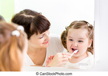 mother kid brushing kid teeth