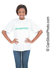 Cheerful woman with hands on hips wearing volunteer tshirt...