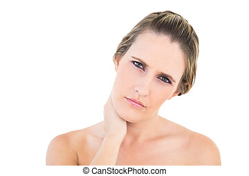 Upset woman looking at camera with a sore neck against white...