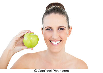 Smiling woman holding green apple looking at camera