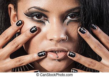Beautiful woman is showing nails. Fashion portrait. Close-up face makeup. Black hair young woman portrait, studio shot