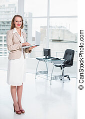 Smiling pretty businesswoman holding laptop at office