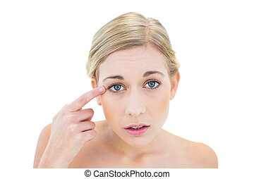 Anxious young blonde woman pointing her eye with her finger...