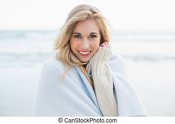 Pleased blonde woman covering herself in a blanket on the...