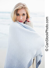 Peaceful blonde woman covering herself in a blanket on the...