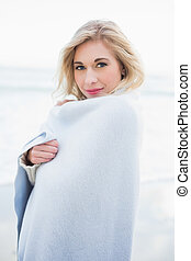 Pleased blonde woman warming herself in a blanket on the...