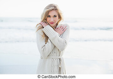 Cute blonde woman in wool cardigan warming up on the beach