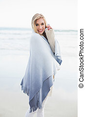 Charming blonde woman covering herself in a blanket on the...