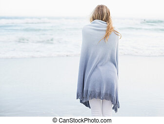 Rear view of a blonde woman warming up in a blanket on the...