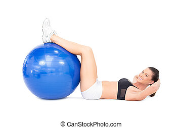 Smiling fit woman developing her abs using exercise ball on...