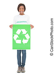 Smiling volunteer woman holding recycling sign