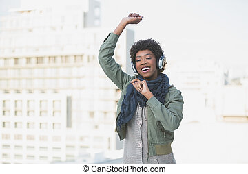 Cheerful casual model dancing while listening to music...