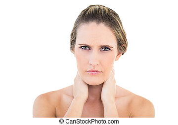 Disgruntled woman looking at camera with a sore neck against...