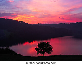 Grayson Lake Dawn - A colorful sunrise sky is reflected on...