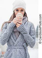 Pretty brunette with winter clothes on drinking coffee...
