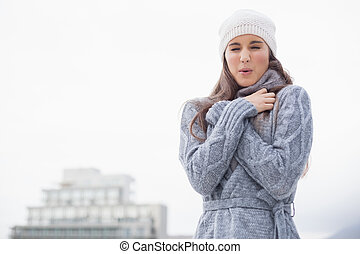 Shivering pretty woman with winter clothes on posing...