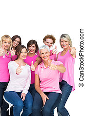 Positive pretty women posing and wearing pink for breast cancer