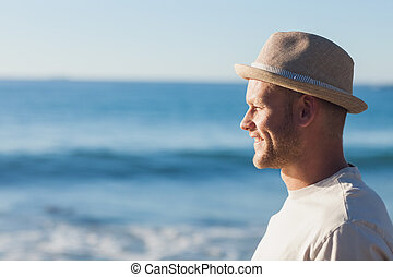 Handsome man wearing straw hat looking at the sea on the...