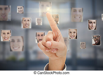 Finger touching futuristic interface showing human faces