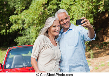 Cheerful mature couple taking pictures of themselves leaning...