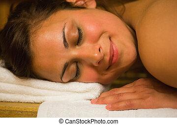 Happy brunette lying in a sauna