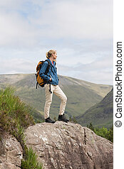 Woman standing on rock admiring the view after a hike in the...