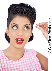 Attractive black hair model using a tweezer on white...