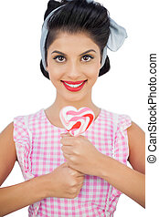 Cheerful black hair model holding a heart shaped lollipop