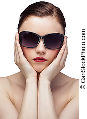 Serious young model wearing stylish sunglasses on white...