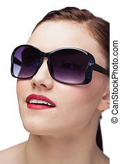 Smiling sensual model wearing classy sunglasses on white...