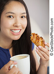 Young asian woman having a pastry