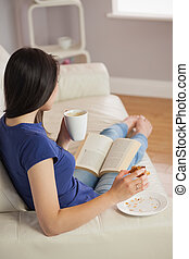 Young woman reading a book and eating pastry with coffee in...