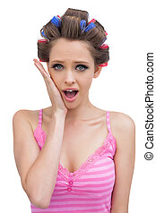 Astonished model with hair curlers on white background