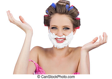 Cheerful woman with hands up and shaving foam on face on...