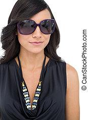 Elegant dark haired model wearing sunglasses on white...