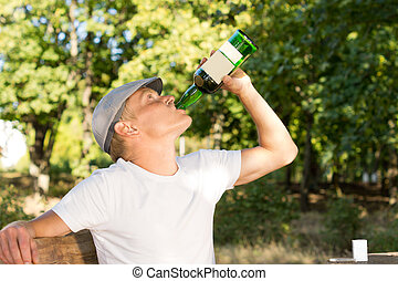 Alcohol abuser drinking from a bottle of wine - Alcohol male...