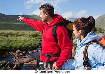 Couple standing at edge of river on a hike with man pointing...
