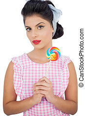Thoughtful black hair model holding a colored lollipop