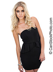 Serious blonde model in black dress posing looking at camera...