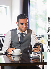Businessman having coffee in restaurant using phone