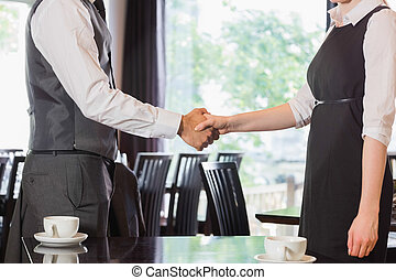 Business people shaking hands after meeting in a cafe