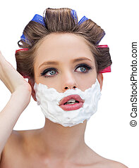 Thoughtful model in hair curlers with shaving foam posing on...