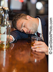 Drunk businessman holding whiskey glass lying on a counter...