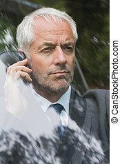 Serious businessman on the phone driving expensive car
