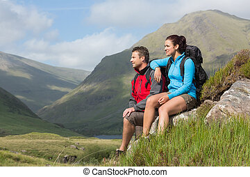 Couple taking a break after hiking uphill in the countryside