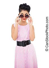 Lovely black hair model looking over her sunglasses on white...