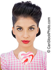 Unsmiling black hair model holding a heart shaped lollipop