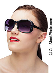 Cheerful sensual model wearing classy sunglasses on white...