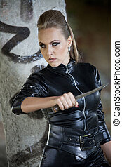 danger girl with knife - woman in sexy leather dress holding...